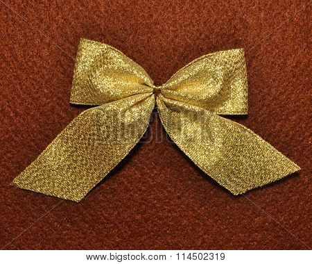 Golden bow on brown felt fabric