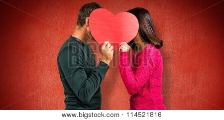 Couple covering faces with heart shape against red background