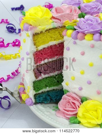 Close up on slice of rainbow layered cake pulled from whole cake