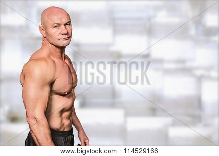Portrait of shirtless bald man against abstract background