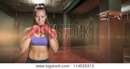 Portrait of pretty woman with fighting stance against red boxing area with punching bags