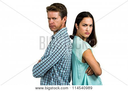Portrait of angry couple standing back to back against white background
