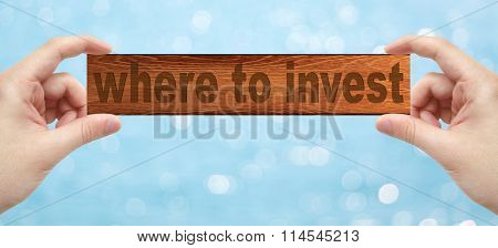 Hands Holding A Wood Engrave With Word Where To Invest