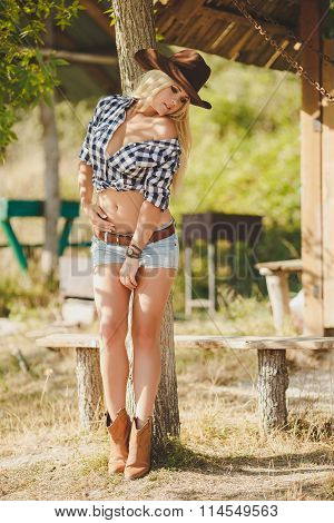 Portrait of beautiful woman - cowboy, on the ranch in the summer
