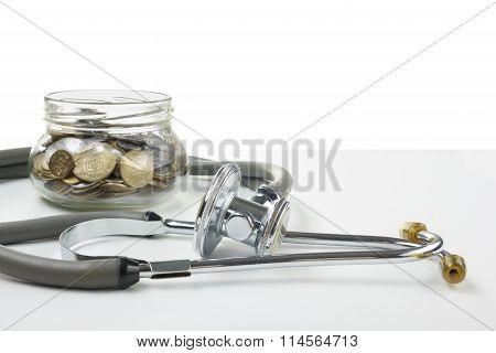 Glass bank with coins, green apple and medical stethoscope. Medical costs, financial concept