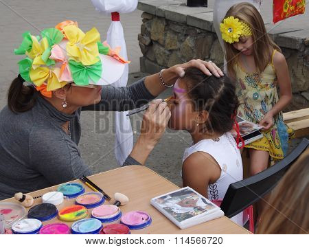 Omsk, Russia - August 03, 2014: face painting process outdoor