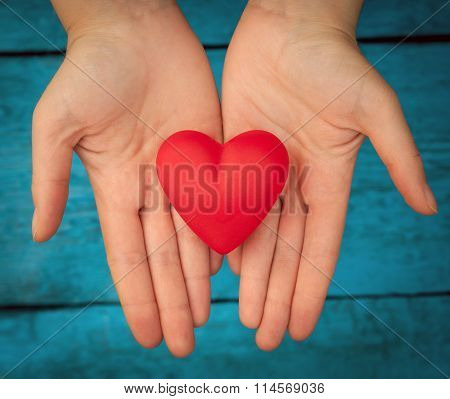 Red heart in the hands