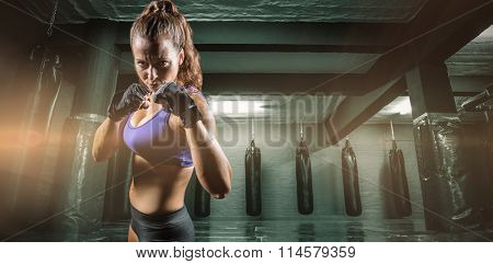 Portrait of woman with fighting stance against red boxing area with punching bags