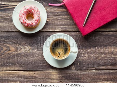 Coffee, Donut And Pink Notepad On Wooden Background
