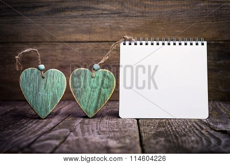 Two Wooden Hearts And Notepad