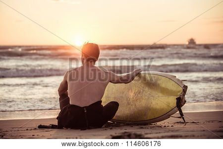 Surfer Taking A Break On The Beach