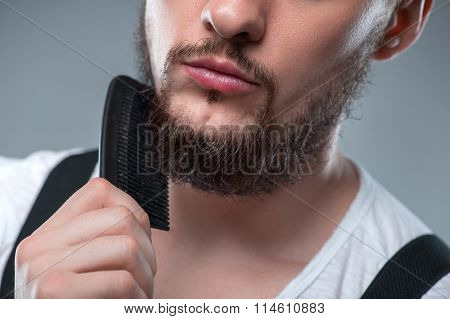Healthy young guy with hairbrush in his hands