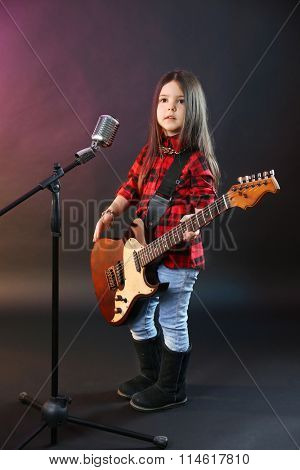 Beautiful little girl with microphone and guitar on dark purple background