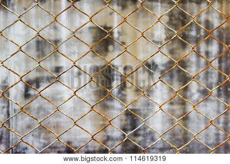 Chainlink fence against wall background, dirty wall