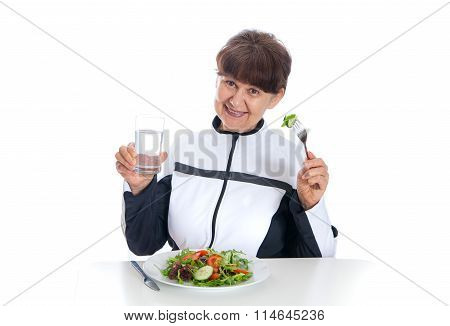 Elderly woman in sport costume eating green salad. Healthy life style concept