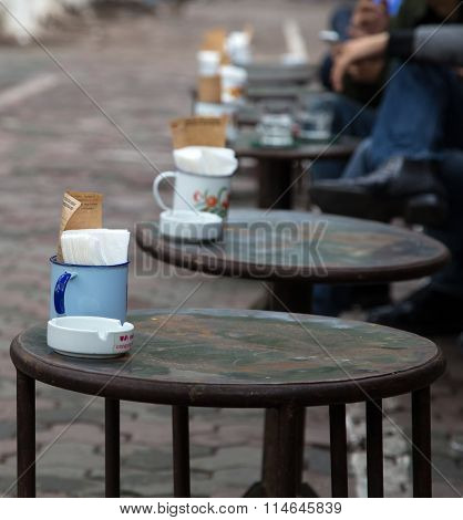 Asian people drinking coffee on the sidewalk