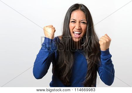 Frustrated young woman baring her fists and yelling in anger with an intense expression upper body on white poster