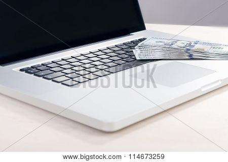 E-trade And E-commerce Ideas And Concepts. Stack Of Banknotes On Laptop In Front Of Open Screen. Foc