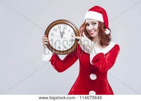 Time And Christmas Holiday Concept And Ideas. Gleeful Red-haired Santa Helper With Big Round Clock A