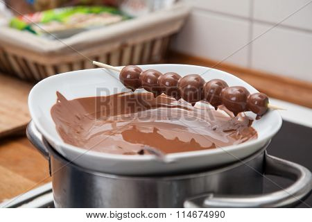 Chcoloate Glazed Grapes On Stick Dripping Into Water Bath