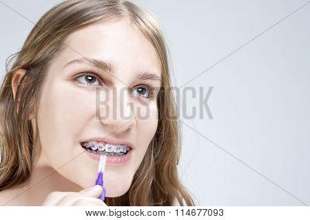 Dental Hygiene Concepts. Caucasian Teenage Girl Using Bristle Teeth Brush For Brackets