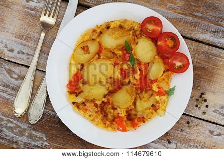 Omelette with potatoes, onions, red pepper and sweetcorn on white plate on rustic wooden surface