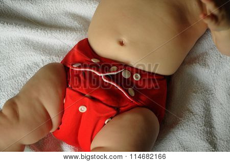 baby with a red cloth diaper on