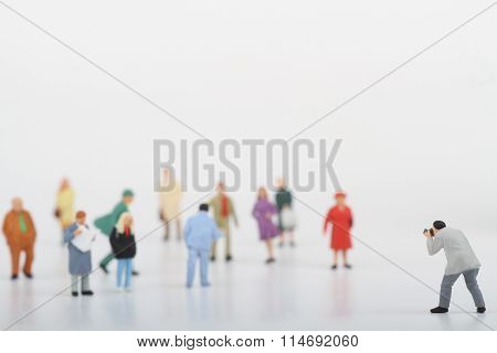 Miniature of a street photographer taking pictures of strangers walking on ta white background