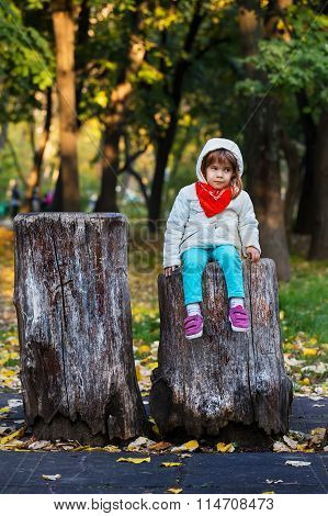 Cute Little Girl Sitting On An Old Log