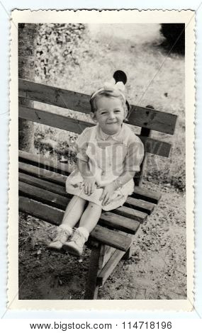 Vintage photo shows a small girl sits on a bench