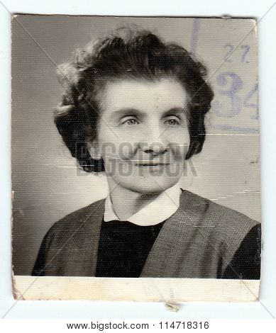A vintage photo shows woman (ID portrait with print of stamp)