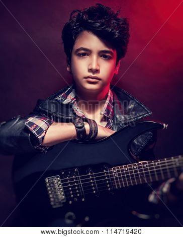 Closeup portrait of serious teen guy playing on guitar in the studio over dark red background, interesting musical hobby