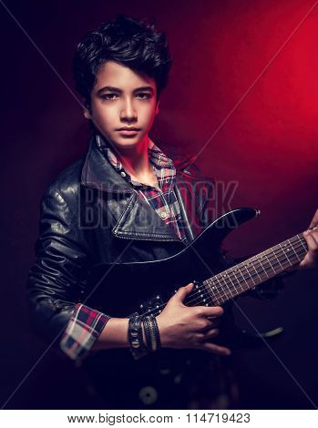 Portrait of handsome guy with guitar over dark red background, wearing stylish clothing and playing popular teen music