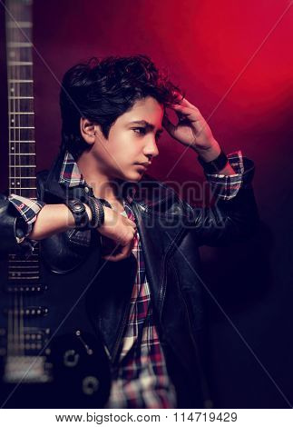 Portrait of attractive teen model posing with guitar in the studio over red background, beautiful guy with trendy hairdo wearing stylish clothing