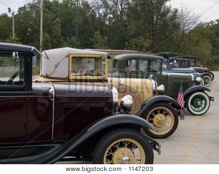 a row of parked eary model antique autos. poster