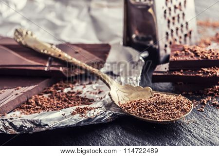 Chocolate. Black chocolate. A few cubes of black chocolate. Chocolate slabs spilled from grated choc