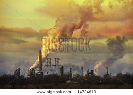 Oil refinery at sunset spewing gases from smoke stacks
