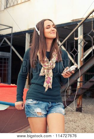 Cute casual smiling woman enjoy listening music with cameraphone on an old pier beside a boat.