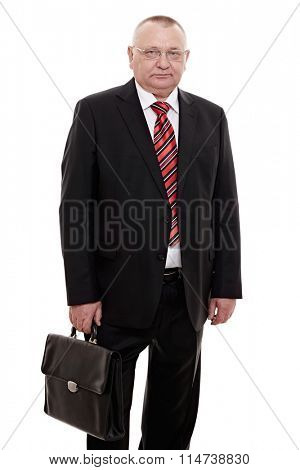 Serious middle aged businessman wearing glasses, red and black striped tie, white shirt and black suit standing with briefcase in his hand isolated on white background - human resources concept