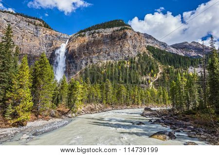 Autumn waterfall forms full-flowing water flow of pearl color. Rocky Mountains of Canada. Yoho National Park