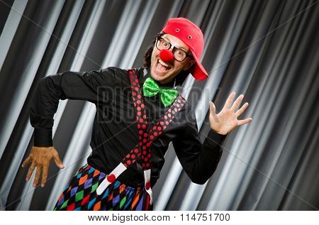 Funny clown in humorous concept against curtain poster
