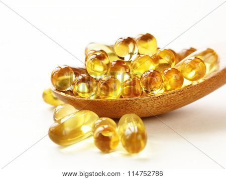 food supplement of fish oil capsules in a wooden spoon - healthy food poster