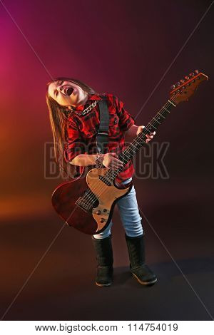 Little rock star playing guitar on dark purple background