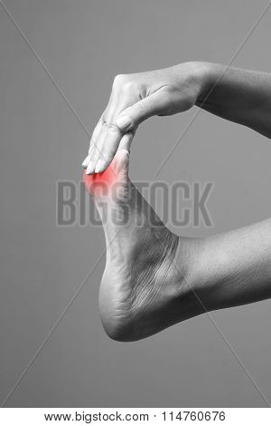 Pain In The Foot. Massage Of Female Feet. Pain In The Human Body On A Gray Background