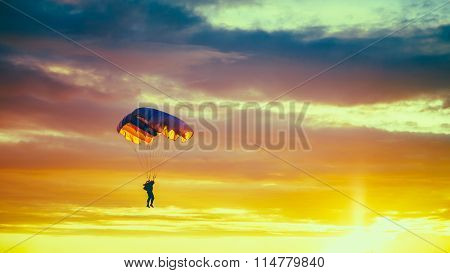 Skydiver On Colorful Parachute In Sunny Sunset Sky. Active Hobbi