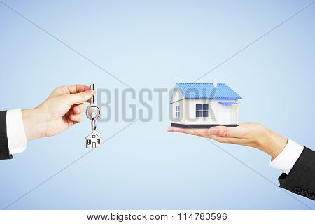Real Estate Concept With Man Hand With Key And House In Another Hand