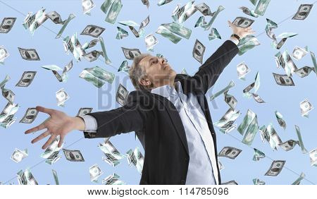 Businessman standing in the rain of money dollar bills