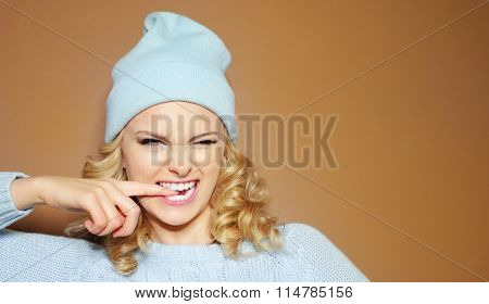 Gorgeous young woman with blond ringlets in a green knitted winter outfit and hat biting her finger