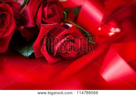 Valentine's Day Red Roses bouquet over silk background. Wedding or Valentines Gift. Art design with bunch of beautiful flowers and red satin ribbon closeup