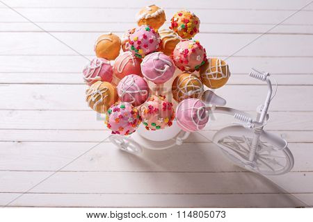 Cake Pops  In Decorative Bicycle On White Wooden Background.
